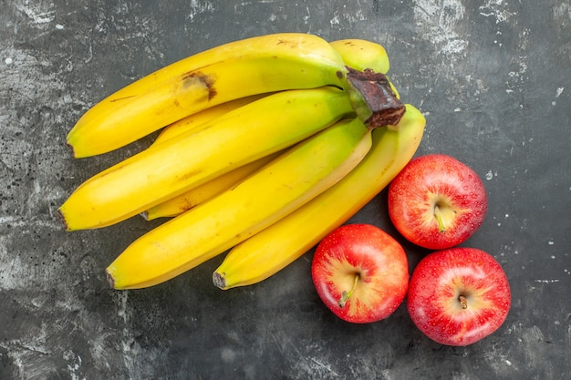 Overhead view of organic nutrition source fresh bananas bundle and red apples on dark background