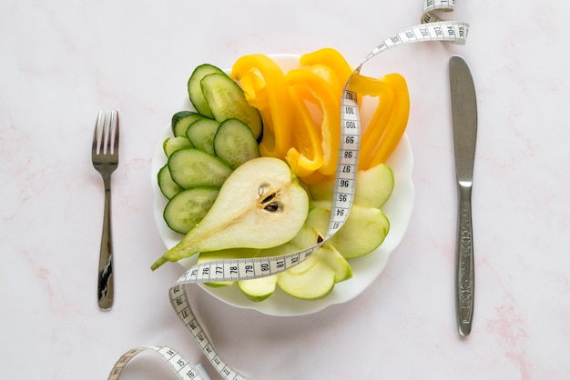 Overhead view of organic slices of vegetable and fruits on plate with measuring tape
