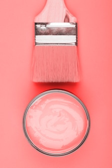 An overhead view of paint coral and paintbrush on colored background