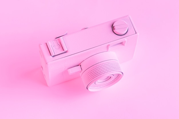 An overhead view of painted camera against pink background