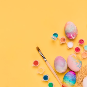 An overhead view of painted easter eggs; paint brush and water color paint on yellow backdrop