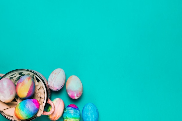 An overhead view of painted watercolor easter eggs on turquoise backdrop