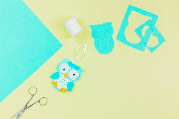 An overhead view of paper owl with thread spool and scissor on yellow background