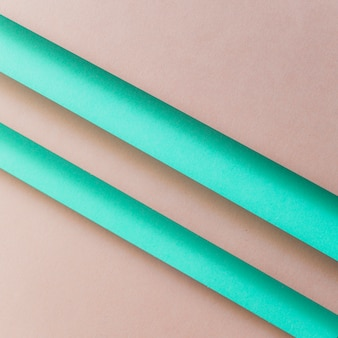 An overhead view of paper turquoise stripes over the brown backdrop