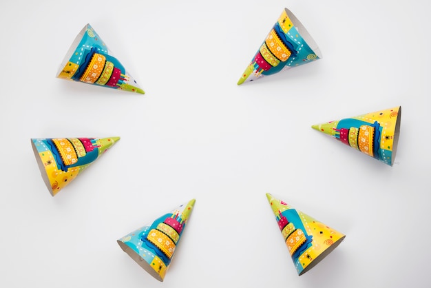 An overhead view of party hats arranged on white background