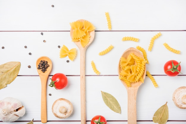 An overhead view of pasta ingredients on white wooden table
