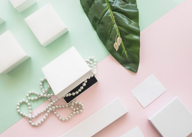 Overhead view of pearl necklace and golden earrings with white boxes on paper background