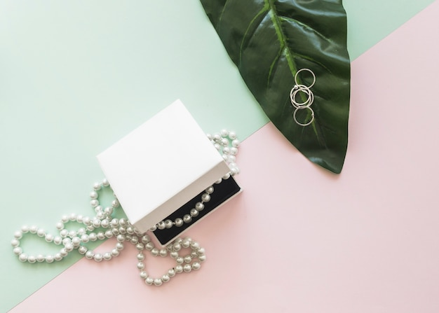 Overhead view of pearl necklace in white box and rings on leaf over the pastel background