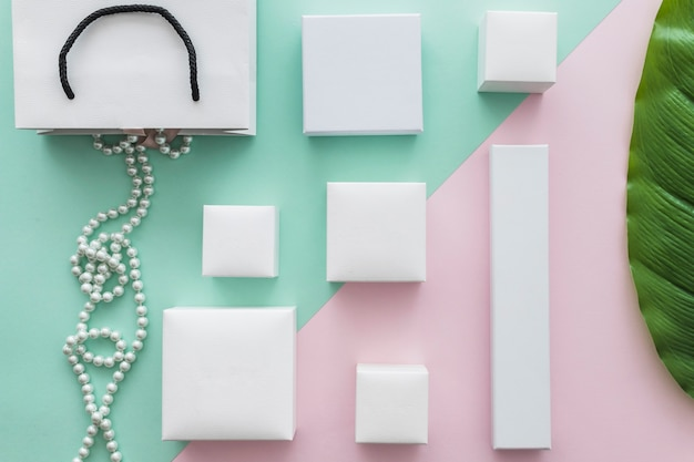 Overhead view of pearls necklace with many white boxes on paper backdrop