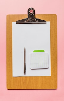 An overhead view of pen and notepad on blank paper over wooden clipboard against pink background
