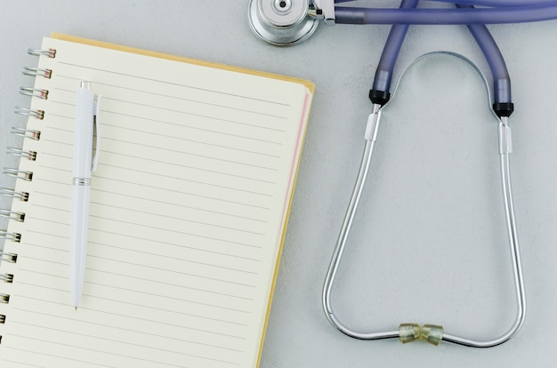 An overhead view of pen over spiral notebook and stethoscope on grey background