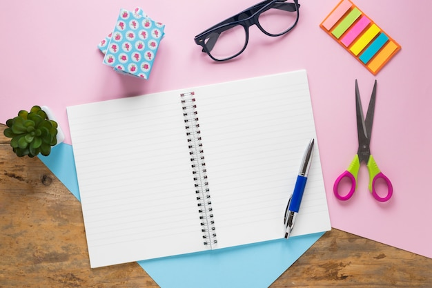 An overhead view of pen on spiral notebook with eyeglasses; scissor on dual backdrop