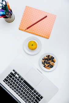 Overhead view of pencil; notebook; citrus fruit; nut food and laptop on white surface