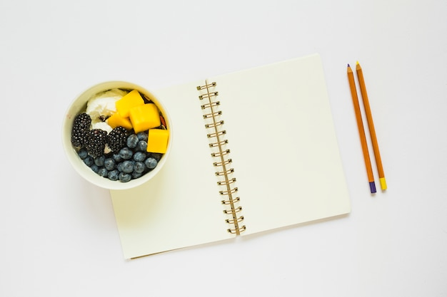 An overhead view of pencils and blank spiral notebook with healthy fruits in cup