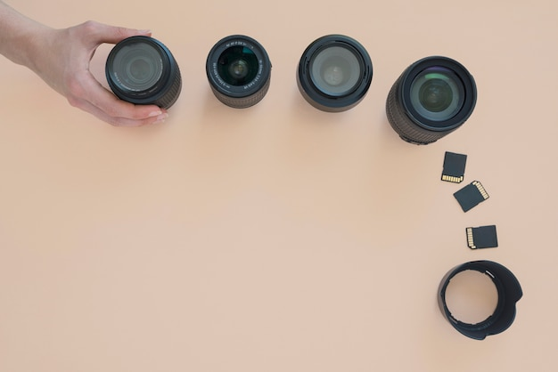 Overhead view of person's hand arranging camera lens; memory card and extension rings over colored background