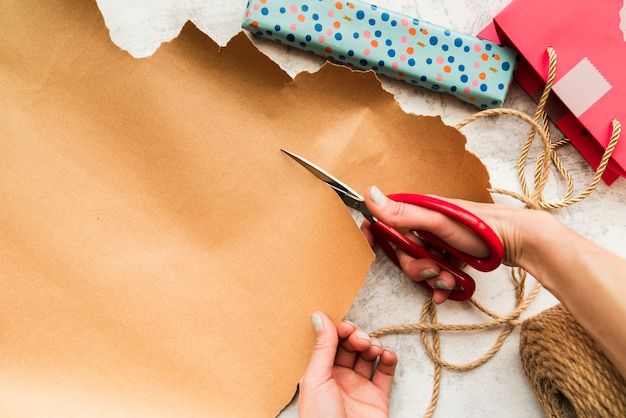 An overhead view of a person 's hand cutting the brown paper with scissor