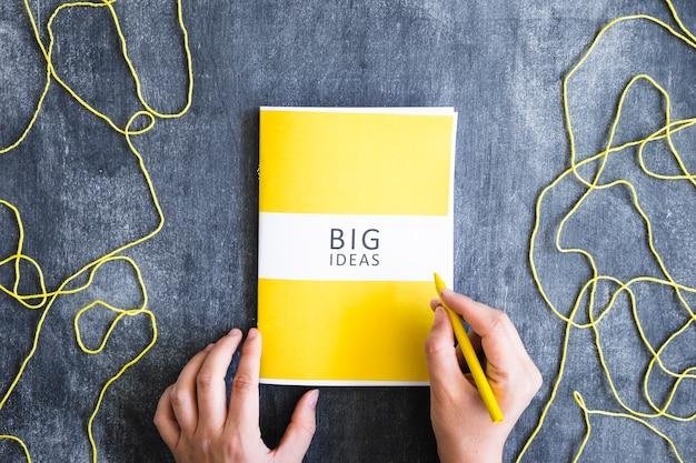 Punto di vista ambientale di una persona che scrive le grandi idee con i pastelli gialli sulla lavagna