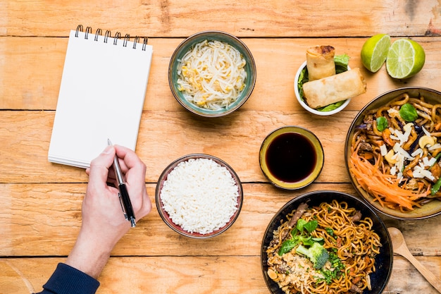 An overhead view of a person writing on pen with spiral notepad with thai traditional food