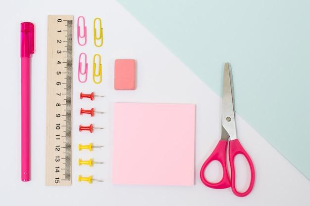 학용품의 오버 헤드 보기 사진입니다. 가위, 스티커, 고무, 눈금자, 종이 클립 및 핀, 흰색 배경에 펜 세트