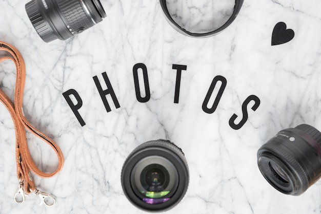 Overhead view of photos text surrounded with camera accessories and heartshape over marble background