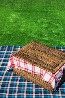 An overhead view of picnic basket on checkered table over green turf
