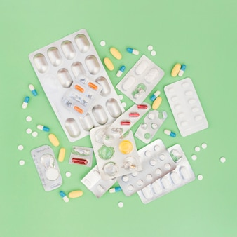 An overhead view of pills and blister pack on green background