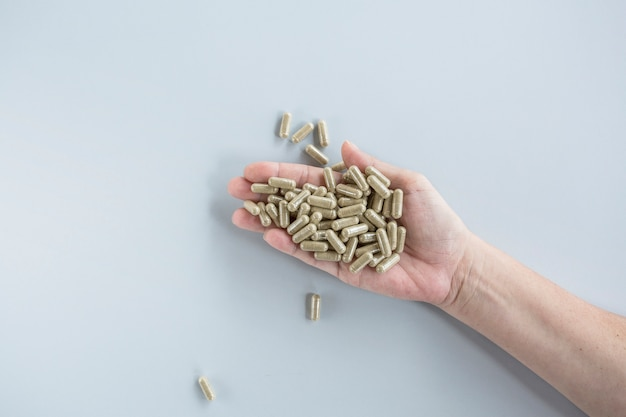 Overhead view of pills in person's hand against grey background