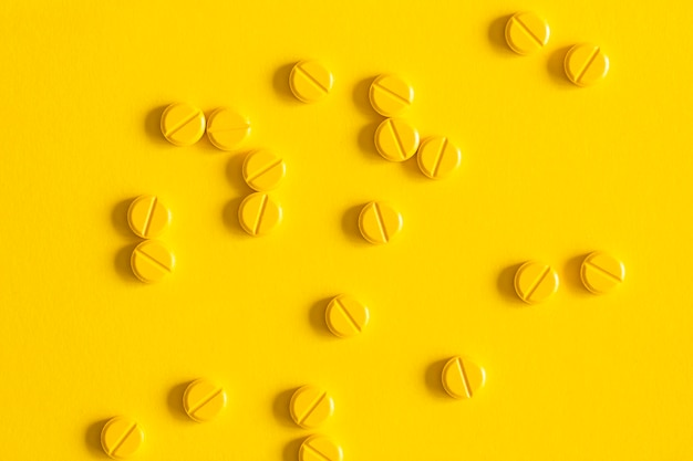 Overhead view of pills scattered over the yellow background