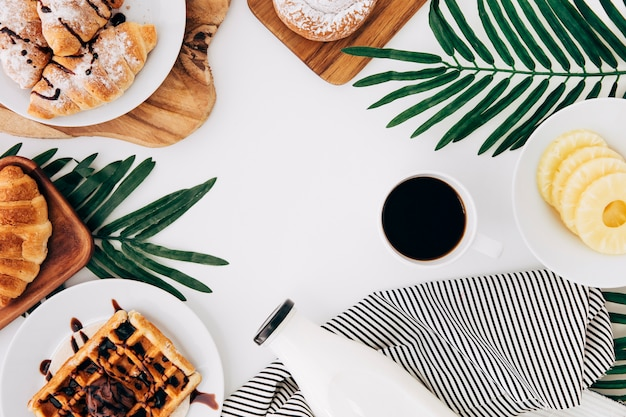 An overhead view of pineapple slices; baked croissant; waffles; buns; tortillas; milk bottle and coffee on white backdrop