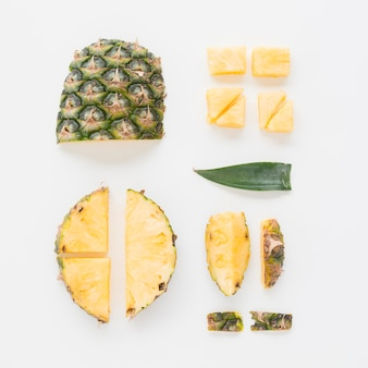 An overhead view of pineapple slices on white backdrop