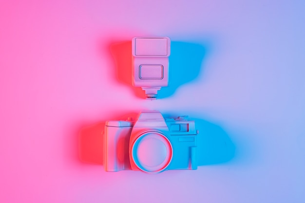 Overhead view of pink camera and lens with shadow and blue light