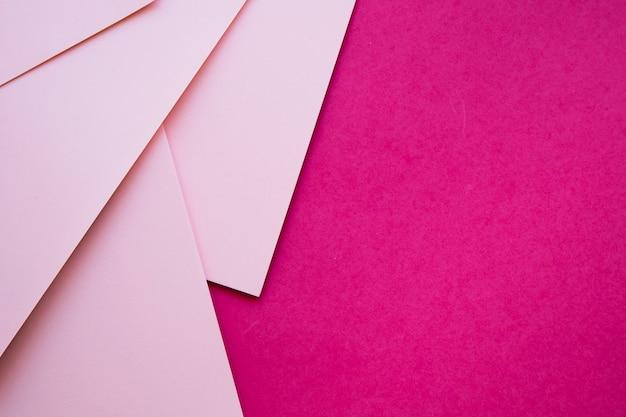 Vista dall'alto di carte di cartone rosa su sfondo magenta