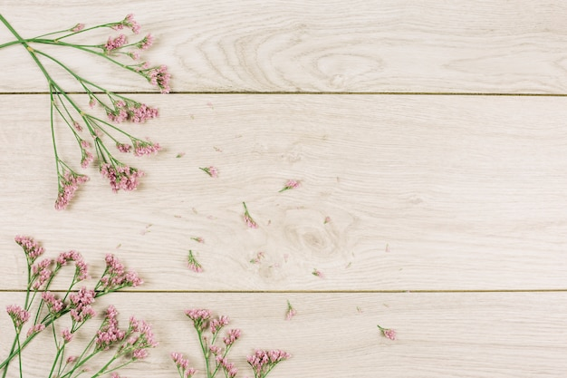 An overhead view of pink limonium flowers on wooden textured surface