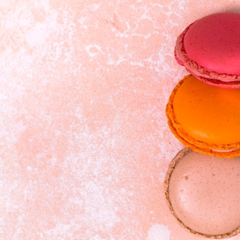 An overhead view of pink; orange and brown macaroons on grunge background