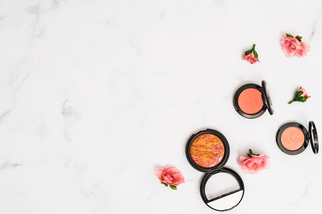An overhead view of pink roses with compact face powder on white textured backdrop