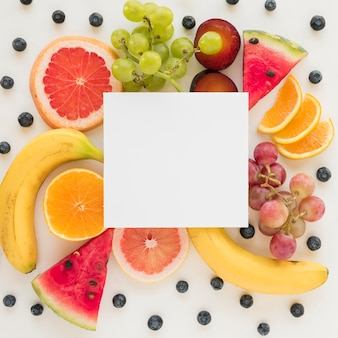 An overhead view of placard over the fresh healthy fruits on white backdrop