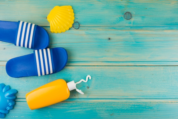 An overhead view of plastic yellow scallop; flip flops and sunscreen lotion bottle on turquoise wooden backdrop