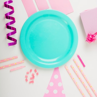 Overhead view of plate surrounded with decorative items on white backdrop