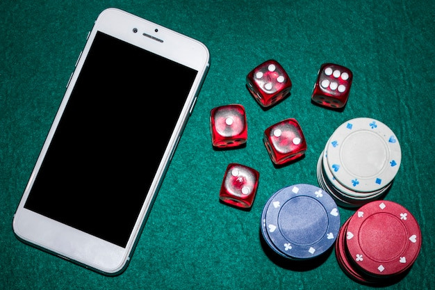 Overhead view of poker table with red dices; casino chips and smartphone