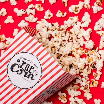 An overhead view of popcorns spilled on red backdrop