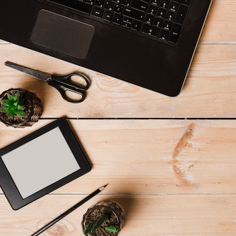 An overhead view of pot plant; pencil; scissor; laptop and ebook reader on wooden table