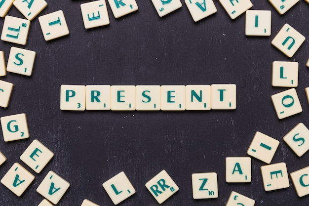 Overhead view of present text on scrabble letters over black backdrop