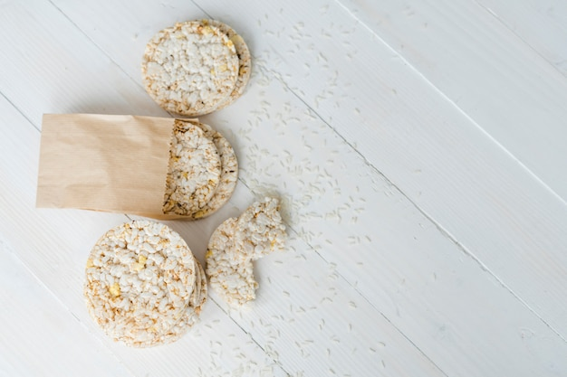 An overhead view of puffed rice with grains on white wooden desk