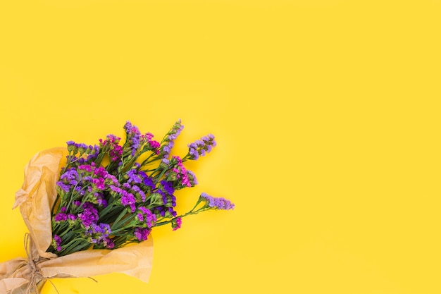 An overhead view of purple flower bouquet on yellow background