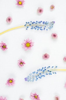 An overhead view of purple mascara and pink flower pattern on white backdrop