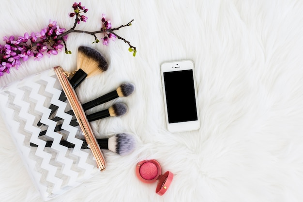 An overhead view of purple twig with makeup brushes; mobile phone and pink compact face powder on white fur