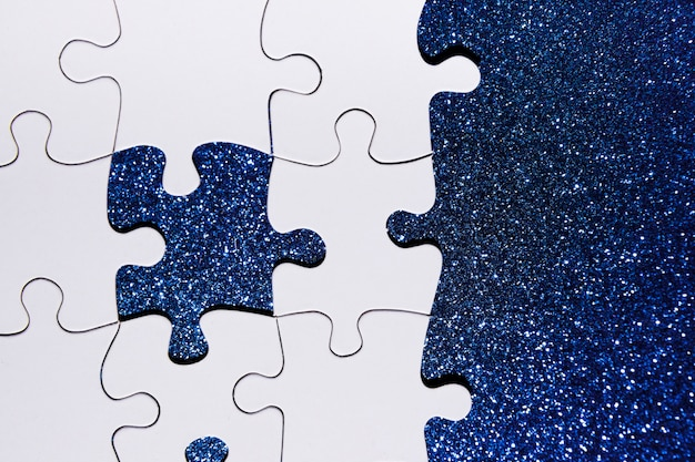 Overhead view of puzzle piece on blue glitter background