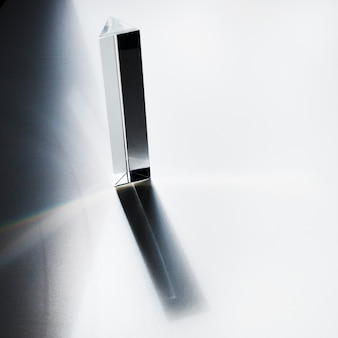 An overhead view of quartz prism with dark shadow on white background