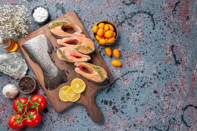 Overhead view of raw fishes lemon slices greens pepper on the right side on wooden cutting board and flower on blue black colors table