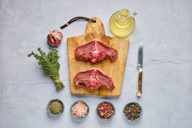 Overhead view of raw fresh deer backstrap with spice and herb over concrete background